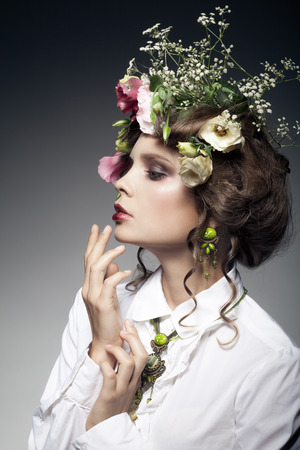 portrait of beautiful young woman with flowers in hair isolated on dark background photo