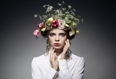 portrait of beautiful young woman with flowers in hair isolated on dark background with copyspace photo