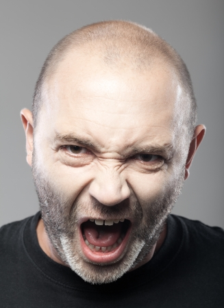 portrait of angry man sreaming isolated on gray background photo