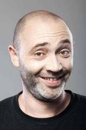 ironic: portrait of ironical smiling man isolated on gray background
