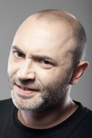 suspicious: portrait of skeptical looking man isolated on gray background