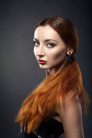 beautiful young redhead woman isolated on dark background photo