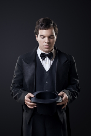tophat: magician showing tricks with top hat isolated on dark background Stock Photo
