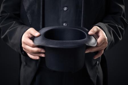어두운 배경에 고립 마술사의 손에 모자의 근접 촬영 스톡 콘텐츠