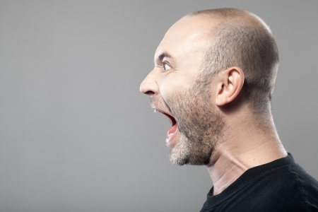 portrait of angry man screaming isolated on gray background with copyspace photo