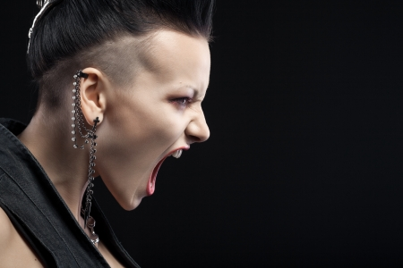 woman screaming: angry young woman screaming isolated on black  Stock Photo