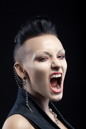 portrait of angry young woman screaming isolated on black background photo
