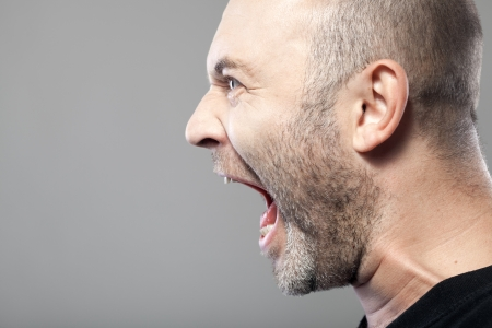 angry man screaming isolated on gray background with copyspace photo