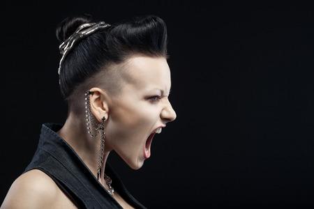 zornige junge Frau schreien isoliert auf schwarzem Hintergrund mit Exemplar