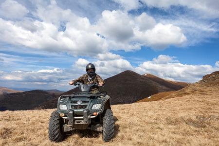čtyři lidé: muž jezdec sedí na ATV na vrcholu hory Reklamní fotografie