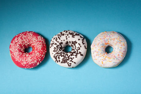 top view of three donuts isolated on blue background with copyspace