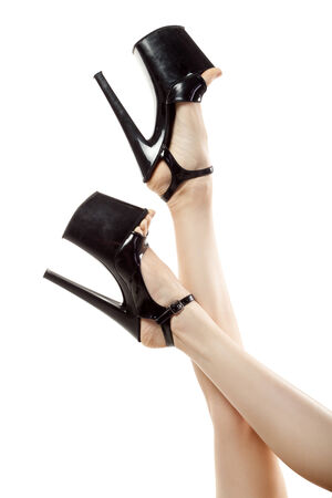 female legs wearing black high heels isolated on white background photo