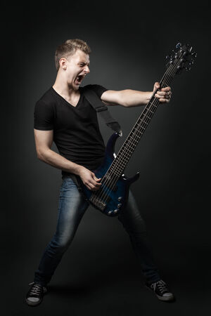 young male musician playing a six-string bass guitar isolated on dark background photo