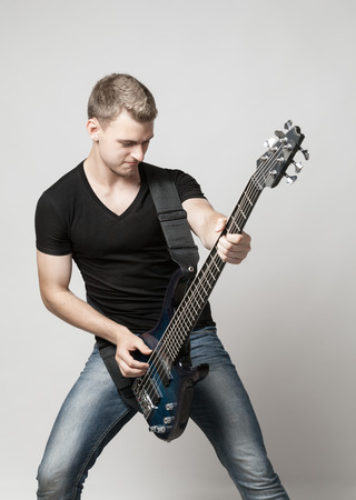 bass player: young male musician playing a six-string bass guitar isolated on light background