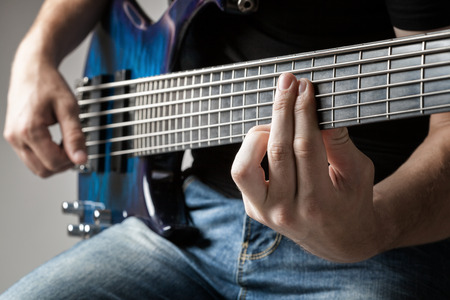 bass player: male musician playing on six-string bass guitar