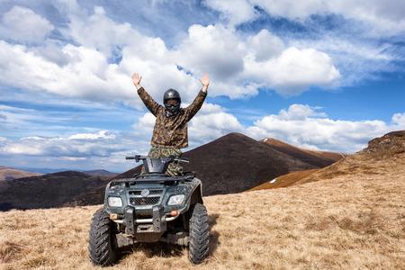 wheeler: male rider on ATV at mountain top