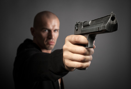 man shooting gun isolated on gray background. focus on gun photo