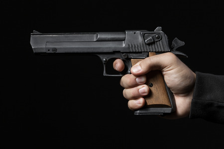 hand gun: male hand with gun isolated on black background Stock Photo