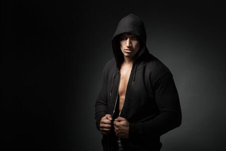 strong man wearing hoodie isolated on black background photo