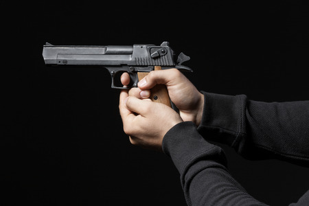 male hands with gun isolated on black background photo