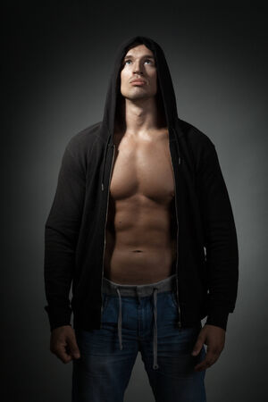 strong man wearing black hoodie isolated on dark background photo