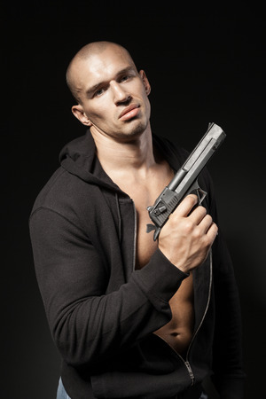 male gangster holding a gun isolated on black background