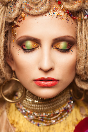 young woman with fashion makeup and closed eyes on brown background photo