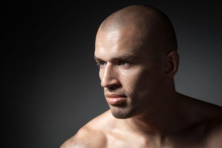 hombre calvo: retrato de hombre fuerte aislado en fondo oscuro