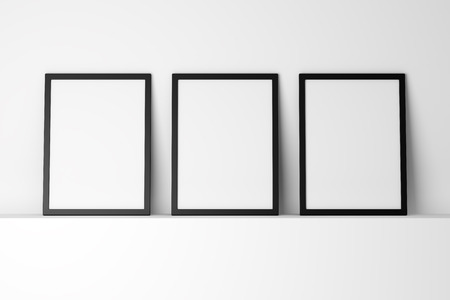 black picture frame: three blank black photo frames on white shelf Stock Photo