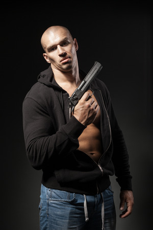 gangster with gun: male gangster holding a gun isolated on dark background