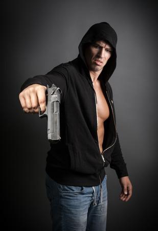 hombre disparando: pistola de tiro hombre aislado sobre fondo gris. foco en el arma