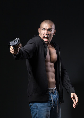 gangster with gun: scared man shooting gun isolated on black background