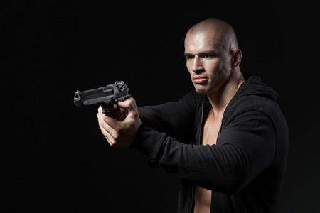 hombre disparando: pistola de tiro hombre aislado en el fondo negro Foto de archivo