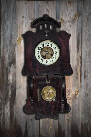 pendulum: old pendulum clock on the background of wooden wall