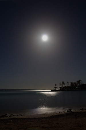 path to romance: tropical night with a full moon over the sea Stock Photo