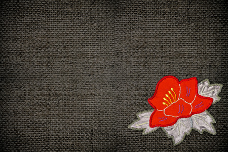 applique flower: gray fabric with a red flower applique closeup Stock Photo