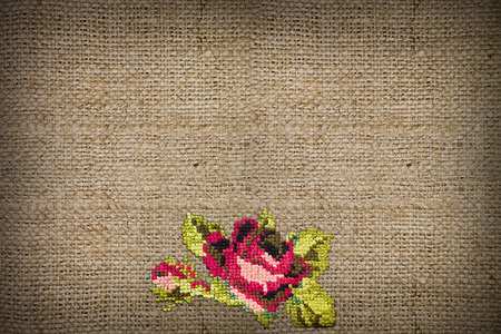 coarse: horizontal background of coarse burlap embroidered cross-stitch rose closeup Stock Photo