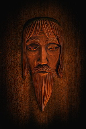 carved wooden mask of an old man in the old Slavic style closeup