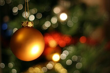 Christmas golden ball with a light blur creating bokeh in the background, natural zoom effect photo