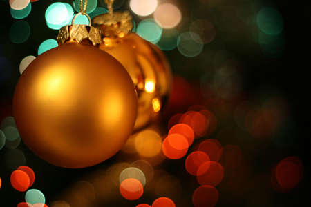 ecard: Christmas golden ball with a red and green light blur creating bokeh in the background Stock Photo