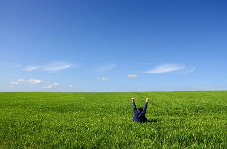 A man sitting alone in a green field, with arms up