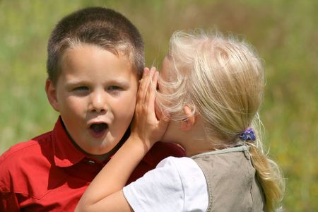 Girl whispering secret to a stunned boy Stock Photo