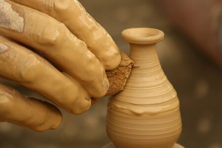 freetime: Close-up of fingers making pottery on a wheel