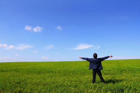 respiration: Seul un homme dans un domaine vert, respirant lair avec les bras ouverts