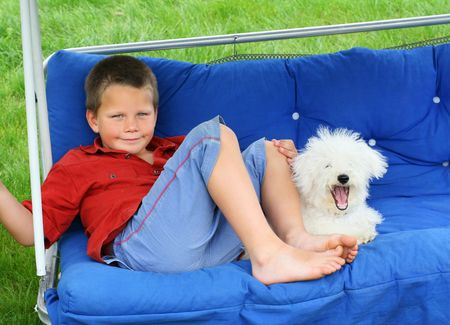 bichon: A blond smiling boy and a yawning puppy relaxing on a porch swing Stock Photo