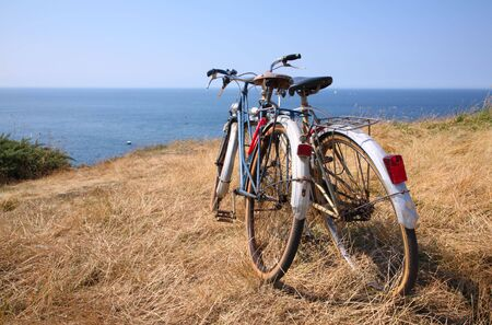 Two attached bicycles near the coast, during holidays in France. Stock Photo