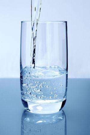 Gießen von reinem Wasser in einem Glas Standard-Bild - 3858794
