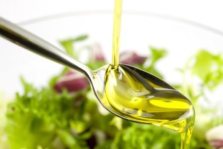 Couler l'huile d'olive dans la salade sur un cuillère