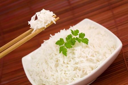 Closeup of rice on chopsticks and a bowl on mat photo