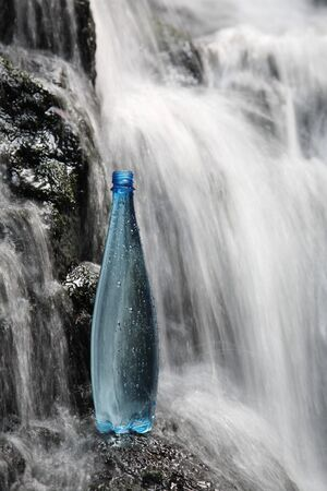 A blue bottle of fresh mineral water in waterfalls photo